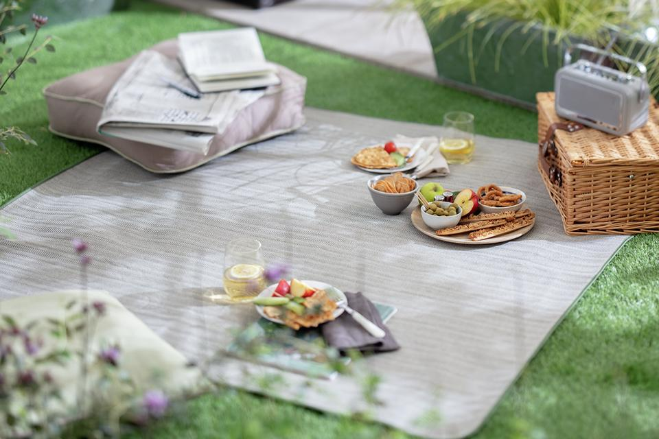 A picnic set up in the garden on a grey blanket with healthy foods like fruit.
