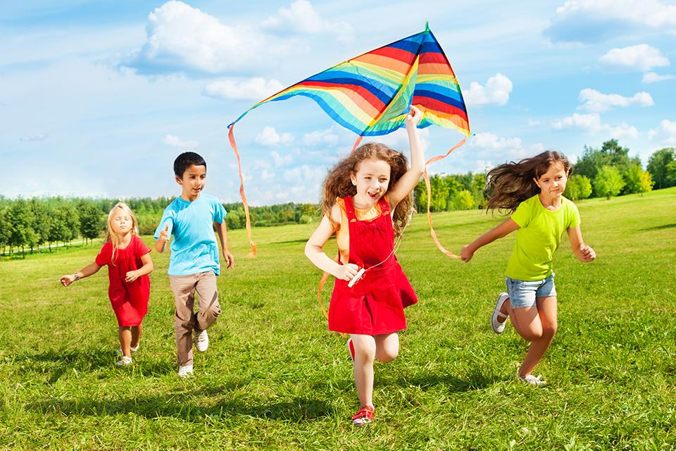 Four children running with one girl trying to launch a colourful kite in the air.