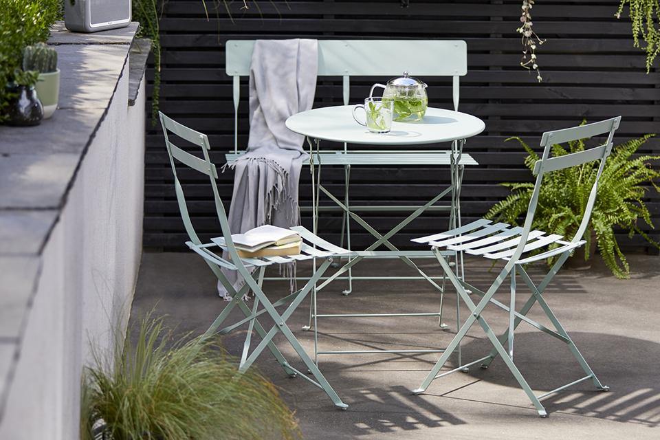 Mint green metal garden chair and table.