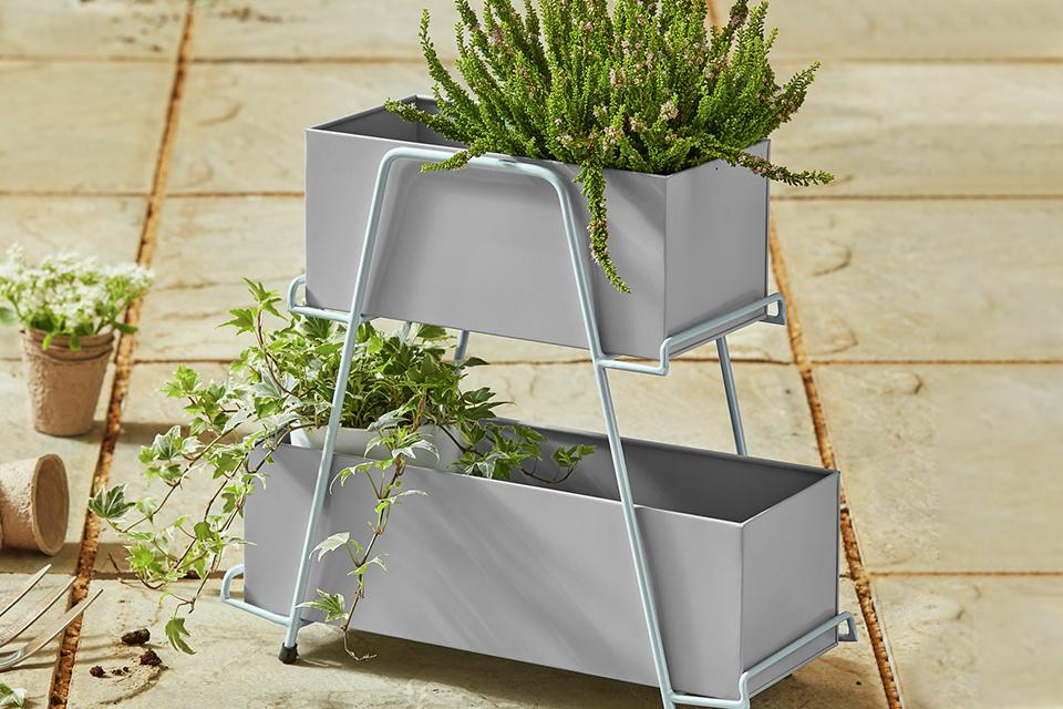 Metal skandi style planter containing two green plants.