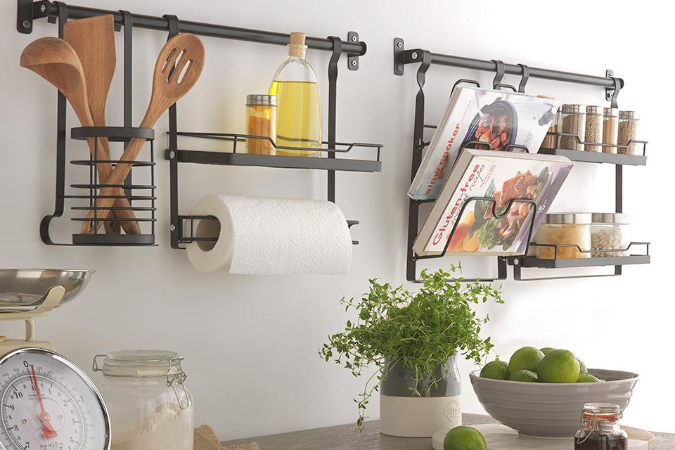 Metal hanging racks for utensils and kitchenware on a white wall.