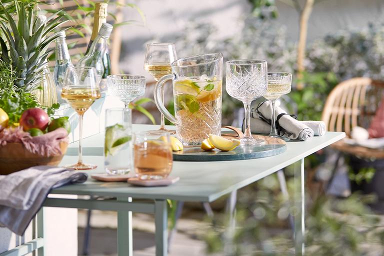 Outdoor table with glassware and cocktails.