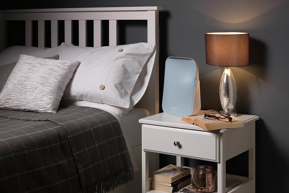 An air purifier on a bedside table next to a bed at night time.