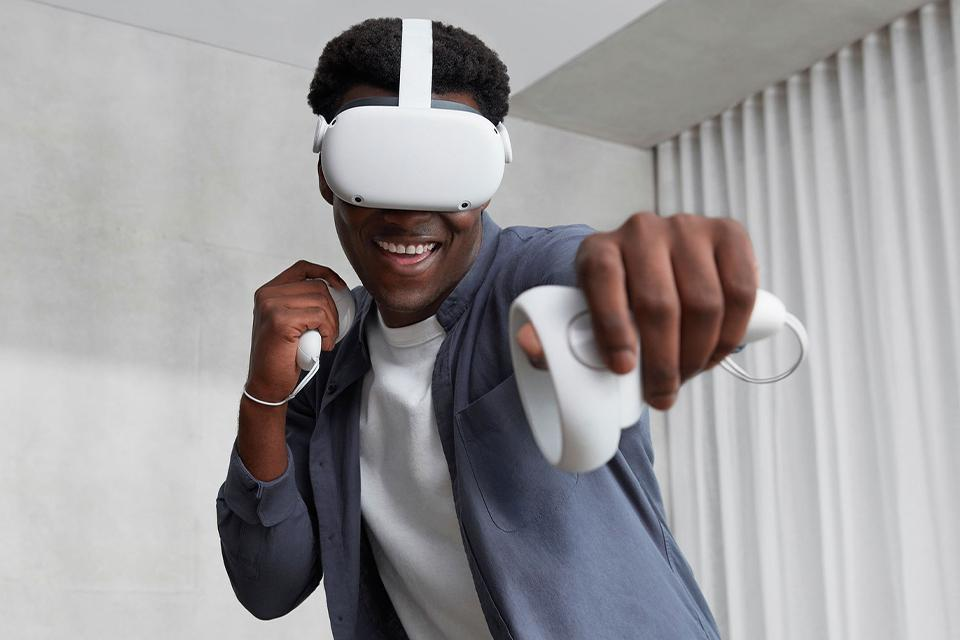A man plays games while wearing an Oculus virtual reality headset.