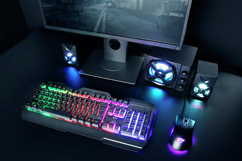 A gaming keyboard and mouse next to a monitor.