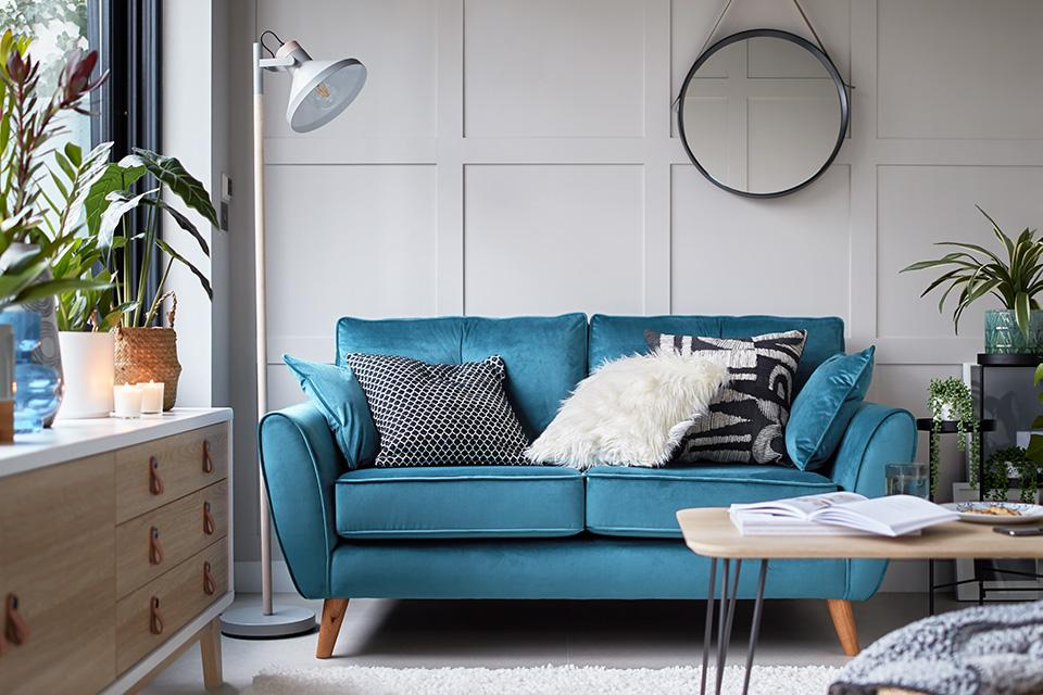 A bright blue, velvet sofa in a living room, with a modern light wood coffee table and sideboard.