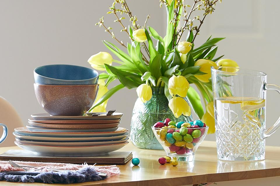 Dining table with yellow flowers and easter eggs.