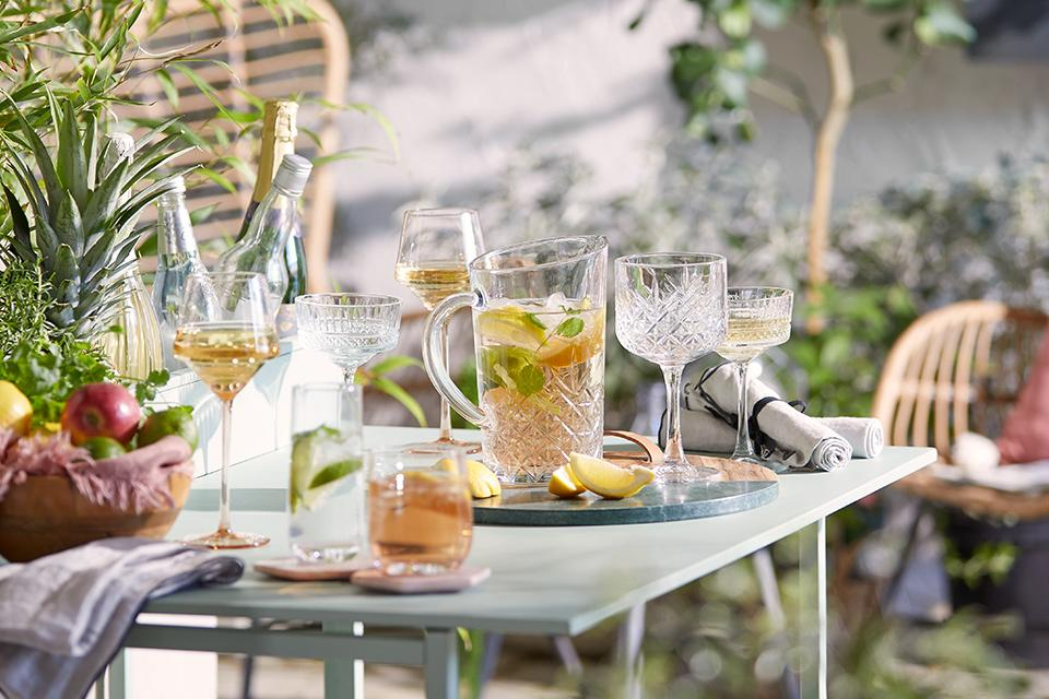 Colourful glassware and tableware in garden.