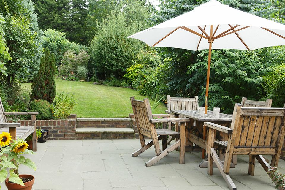 White parasol up above a wooden garden table.