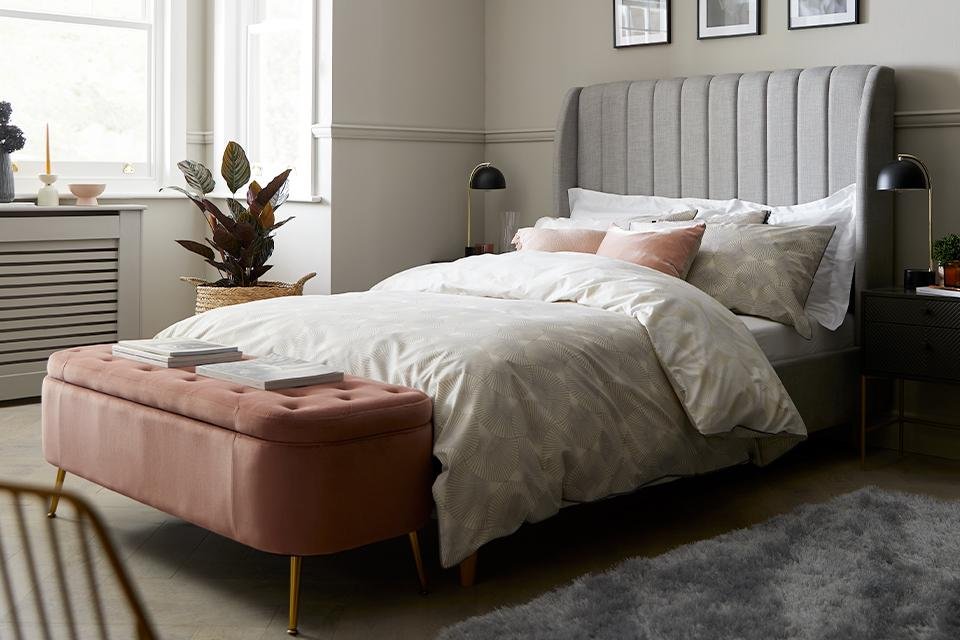 Grey high headboard bed with pink ottoman storage.