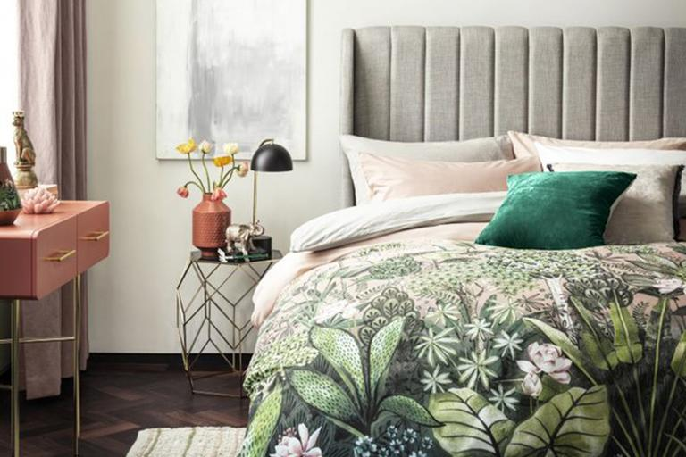 Green floral bedding on grey velvet bed.