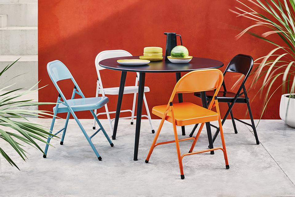 Four coloured folding chairs around table outside.