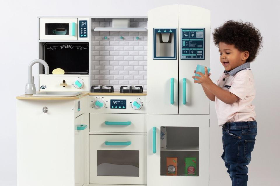 Little boy playing with the Chad Valley deluxe wooden kitchen with breakfast bar.