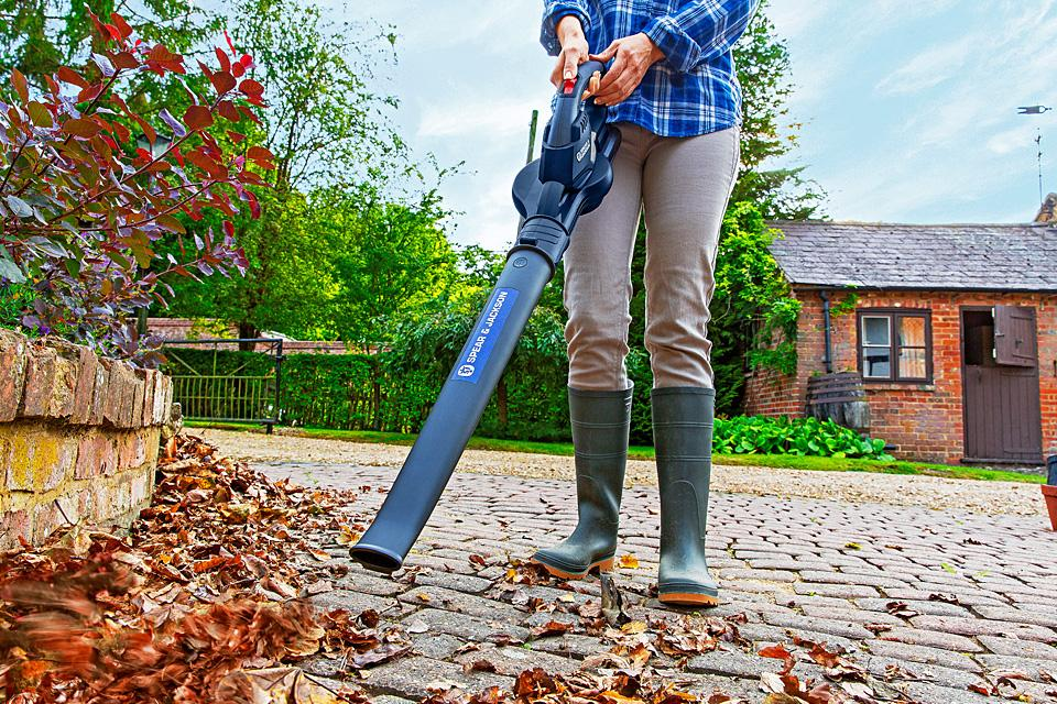 Woman using garden vac to blow leaves off path.
