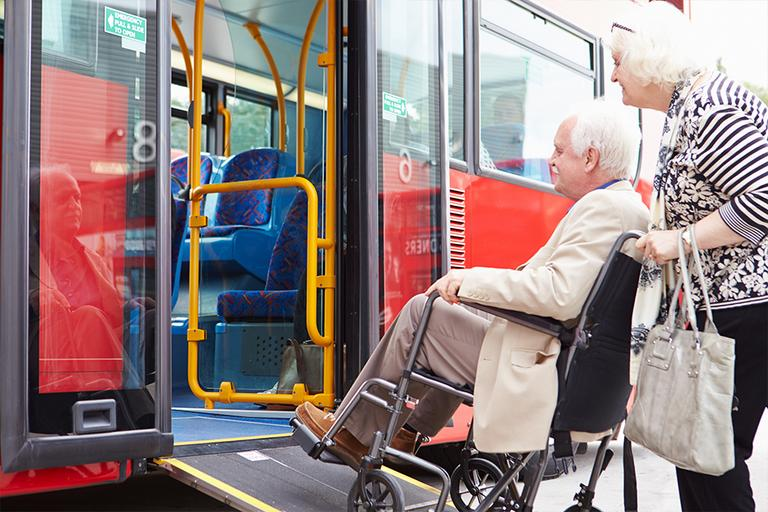 Elderly man being wheeled onto a bus.