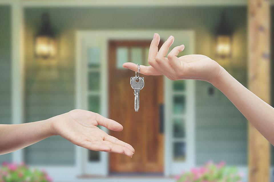 Person handing over keys to someone else for a house.