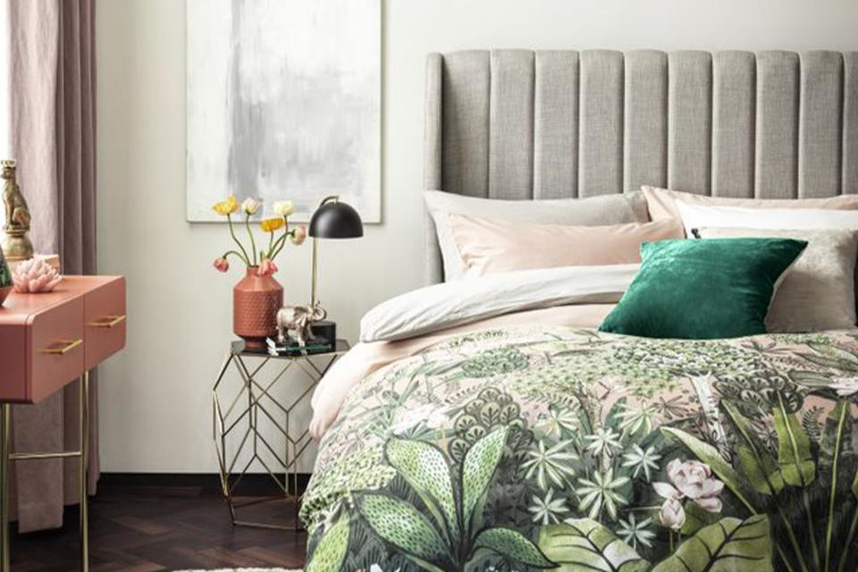 Green floral bedding on grey high headboard bed.