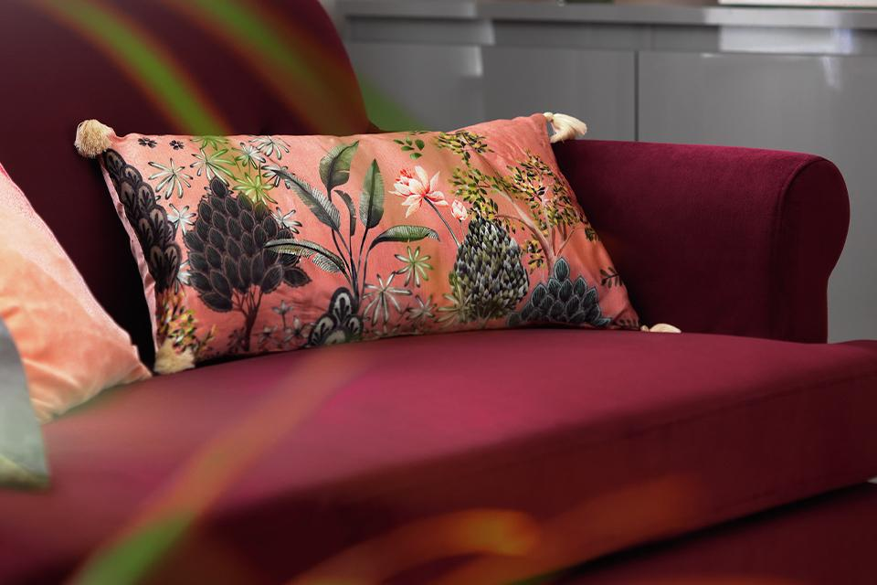 A pink garden print tassel cushion on a burgundy sofa.