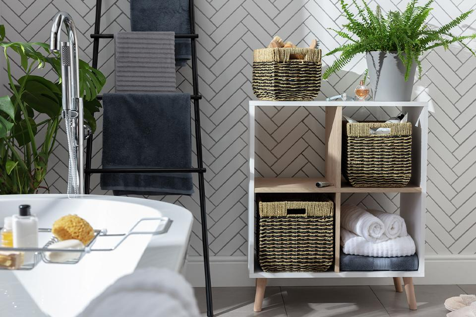 Seagrass baskets in a white 4 by 4 cube shelving unit.