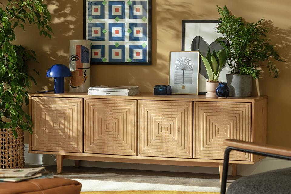 A grooved wooden sideboard with decor on top.