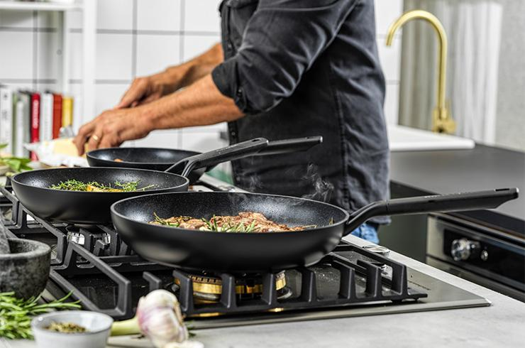 Man cooking using 3 different sized pans.