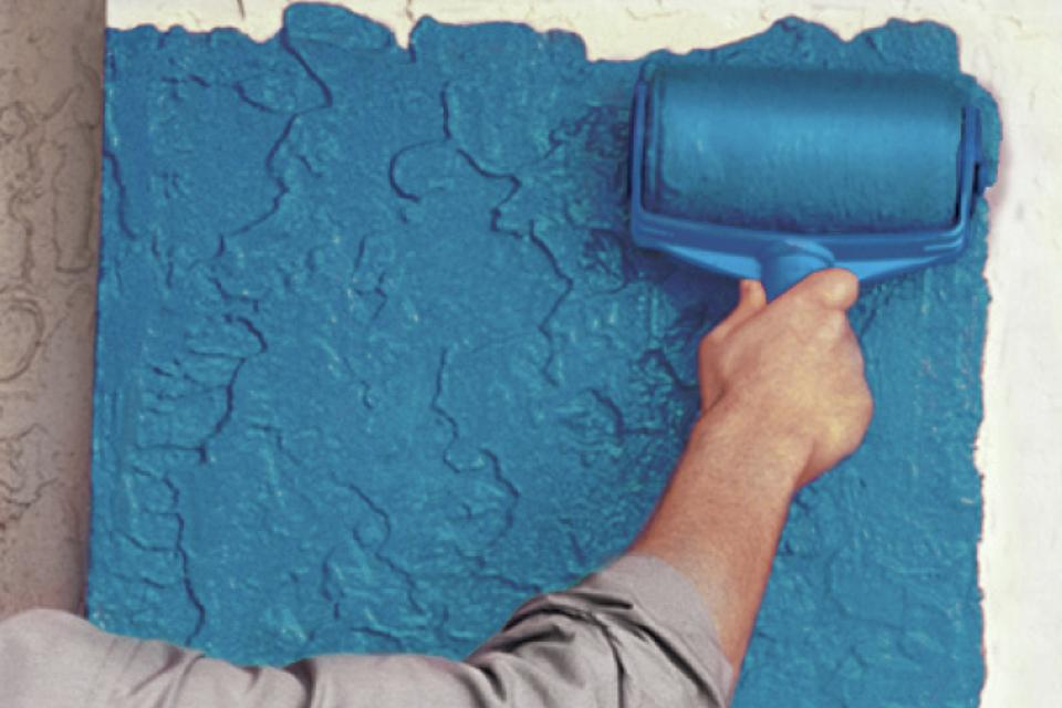 Person painting a wall blue.