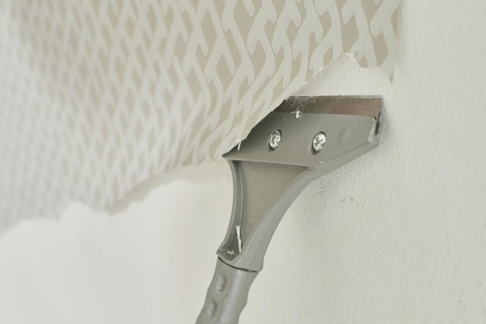 A metal scraper scraping wallpaper off a wall.