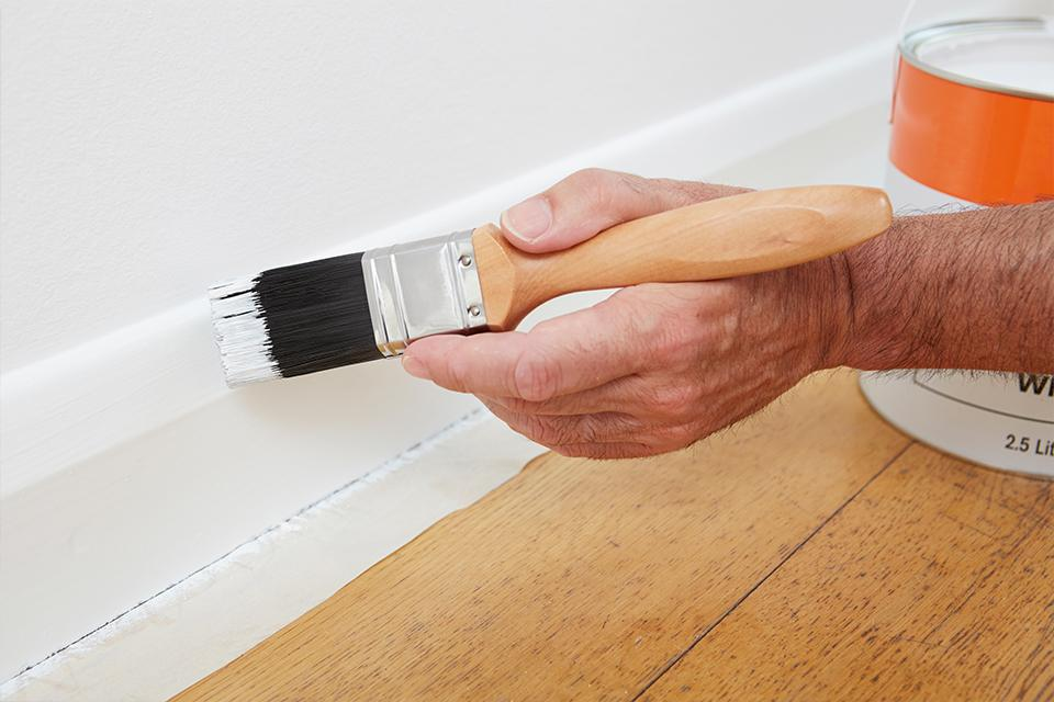 Person painting white gloss onto a skirting board.