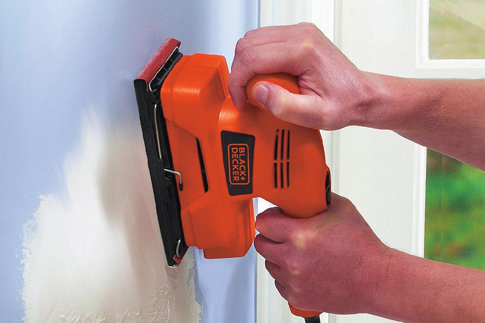 Man using a sander on wall.