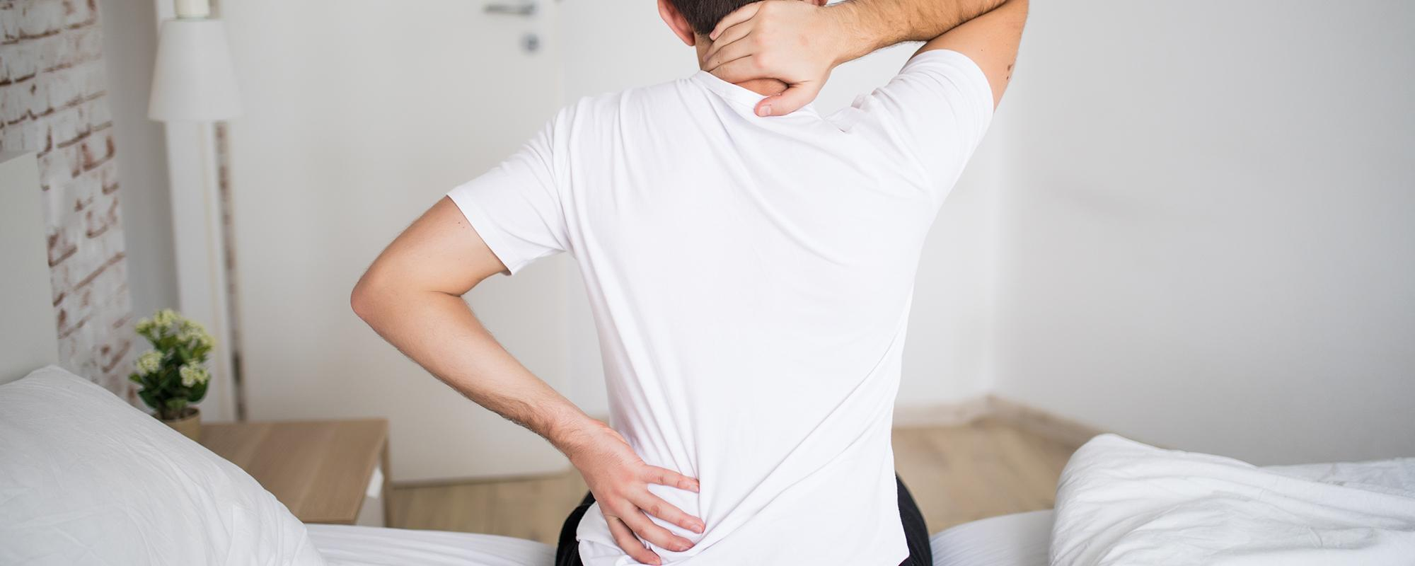 Man suffering from back pain at home in the bedroom.