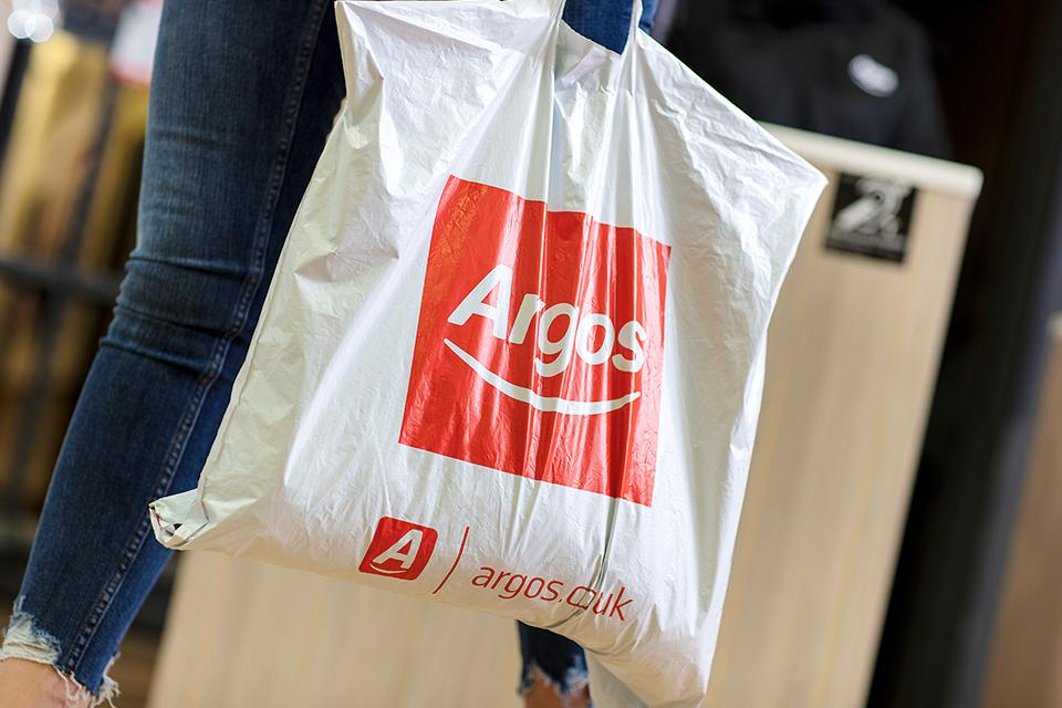 An Argos carrier bag being carried.