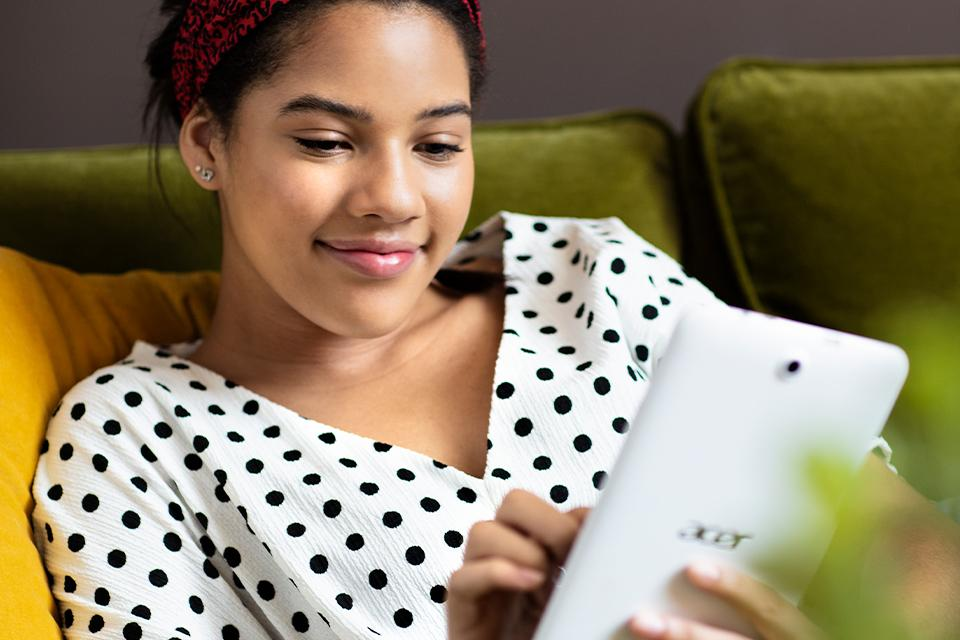 Woman sitting on sofa, looking at phone and smiling.