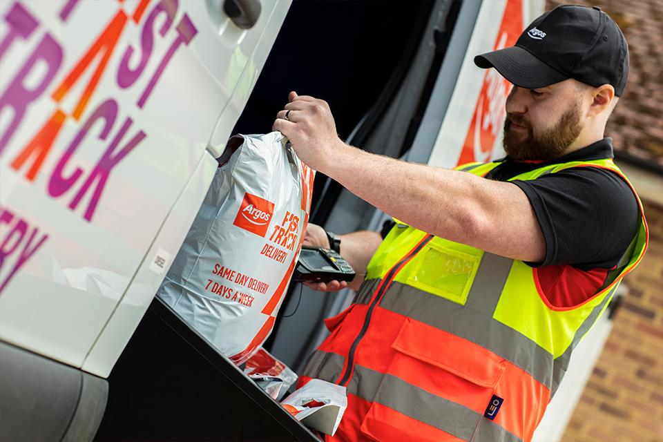 An Argos driver scans a Fast Track package.