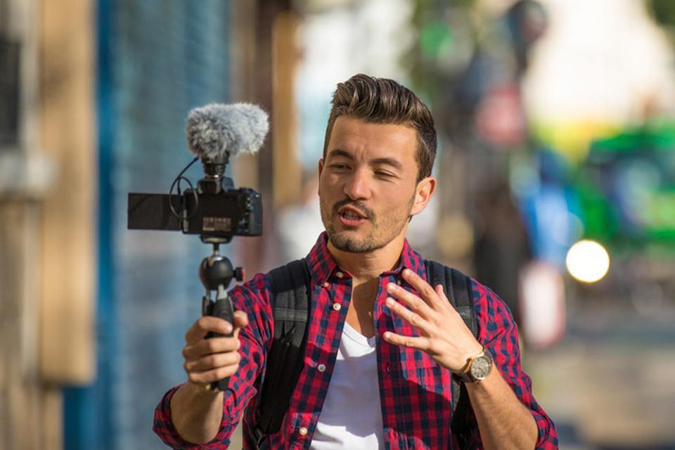 A man is show holding a camera and facing it towards himself.