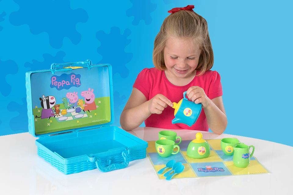 A girl in a pink top plays with a Peppa Pig tea set. Cups, spoons and a milk jug are laid out on a picnic mat, and the tea set box is open to reveal a picture of Peppa and her friends inside the lid.