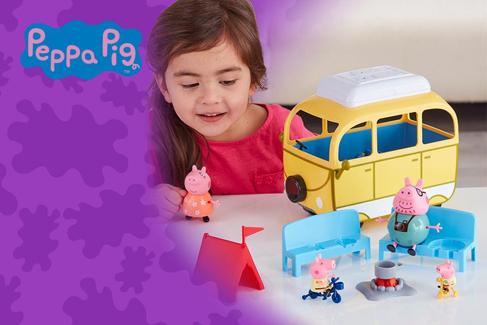 Small girl playing with a Peppa Pig camper van.