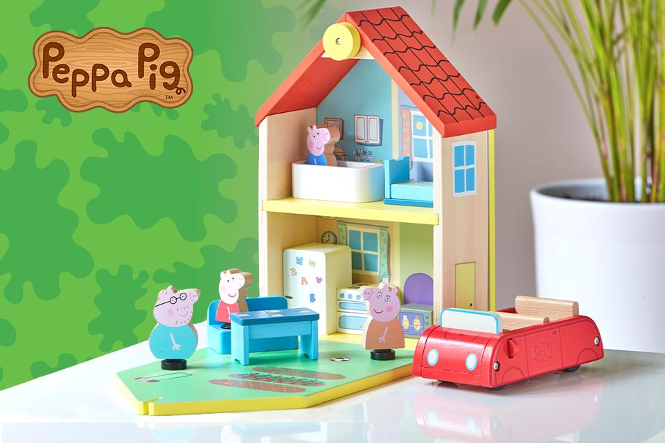 A wooden Peppa Pig house is displayed next to a pot plant. One wall is open, allowing you to see wooden models of Peppa and family inside different rooms.