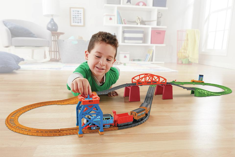 Young boy led on floor in living room playing with the Thomas & Friends 3 in 1 Playset.