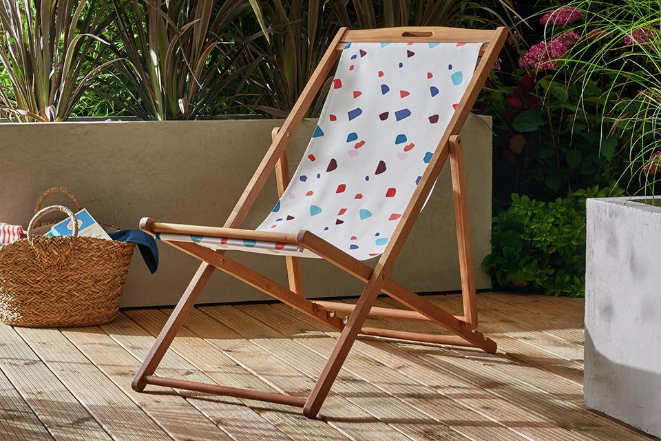 White patterned deck chair in garden.