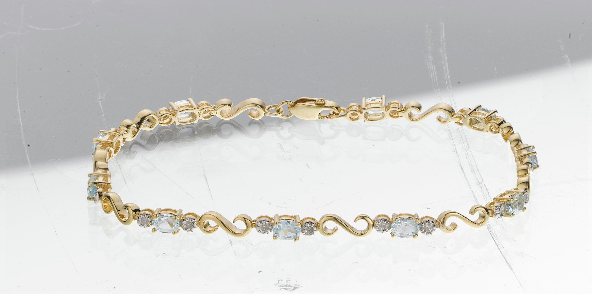 9 Carat Gold - Blue Topaz and 0.10 Carat Diamond Bracelet.