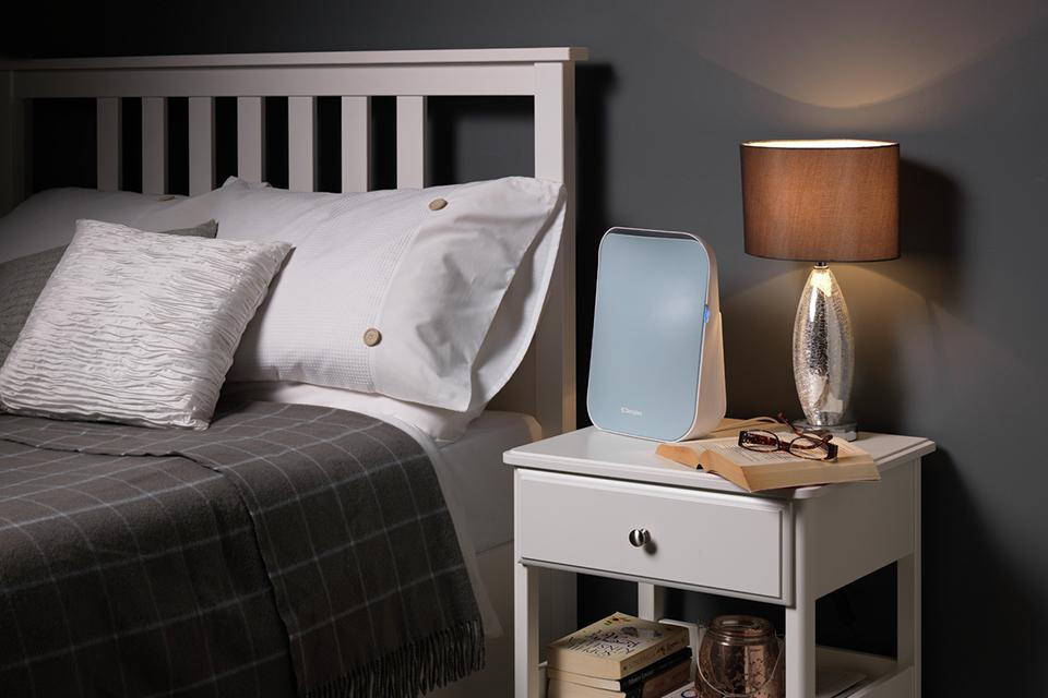 An air purifier on a bedside table.