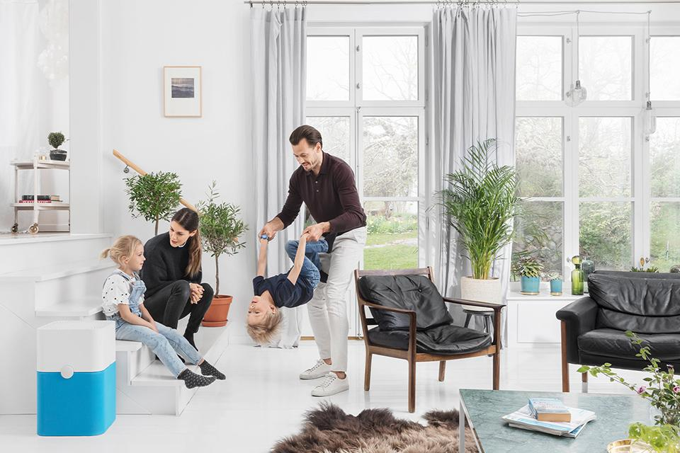 A family sitting and playing in a living room containing an air purifier.