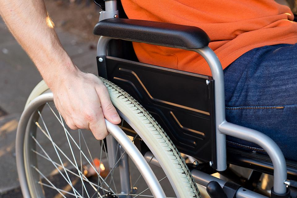 Person in wheelchair pushing wheels.