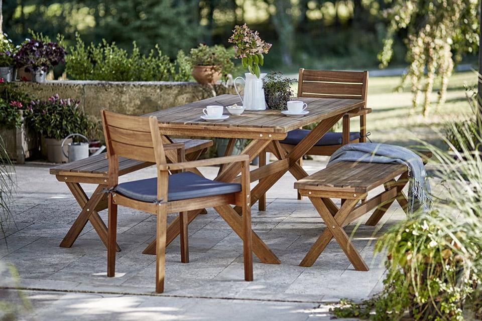 A wooden garden patio set, with 2 chairs and 2 benches.