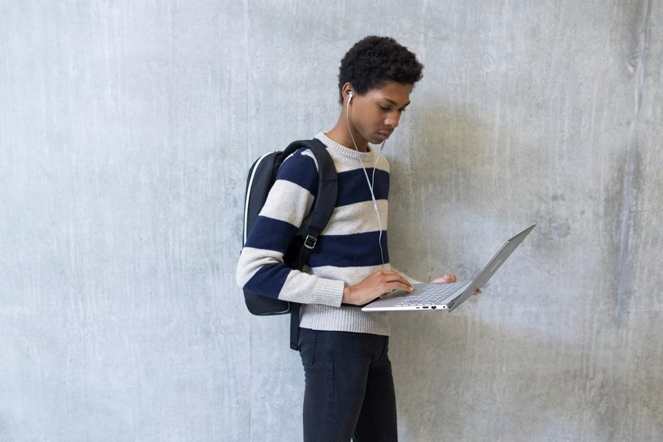 Student standing against wall holding laptop.