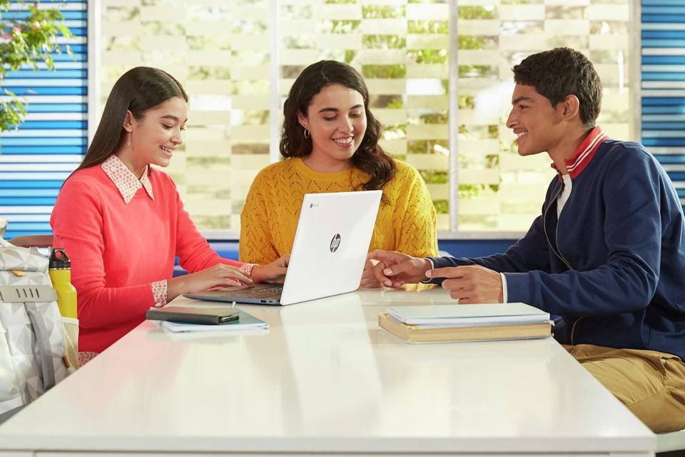 A group of three students using a Chromebook on a group project.