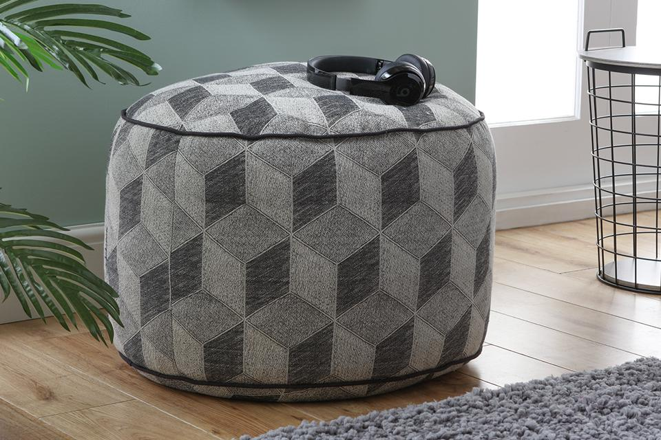 A geometric patterned footstool in a living space.