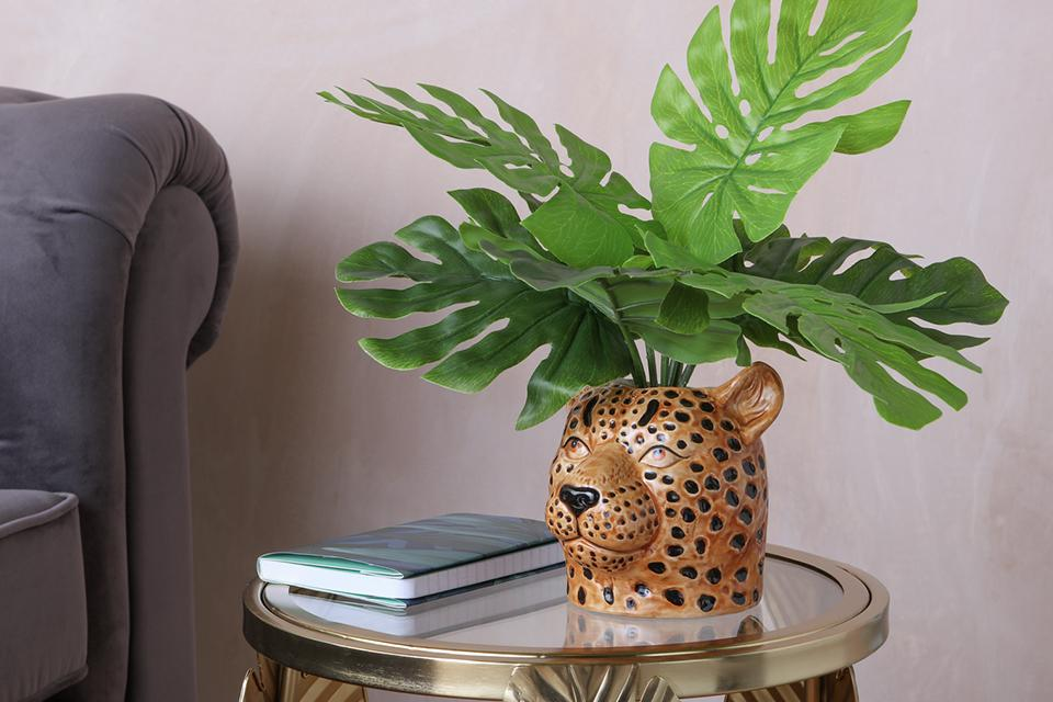 An artificial plant in a leopard head planter on a side table.