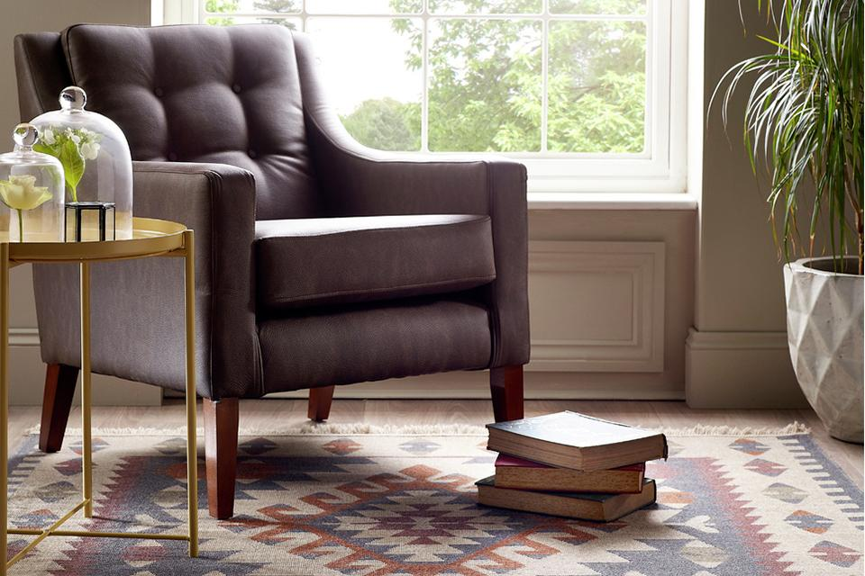 A comfy armchair positioned by a window on top of a brightly patterned rug.