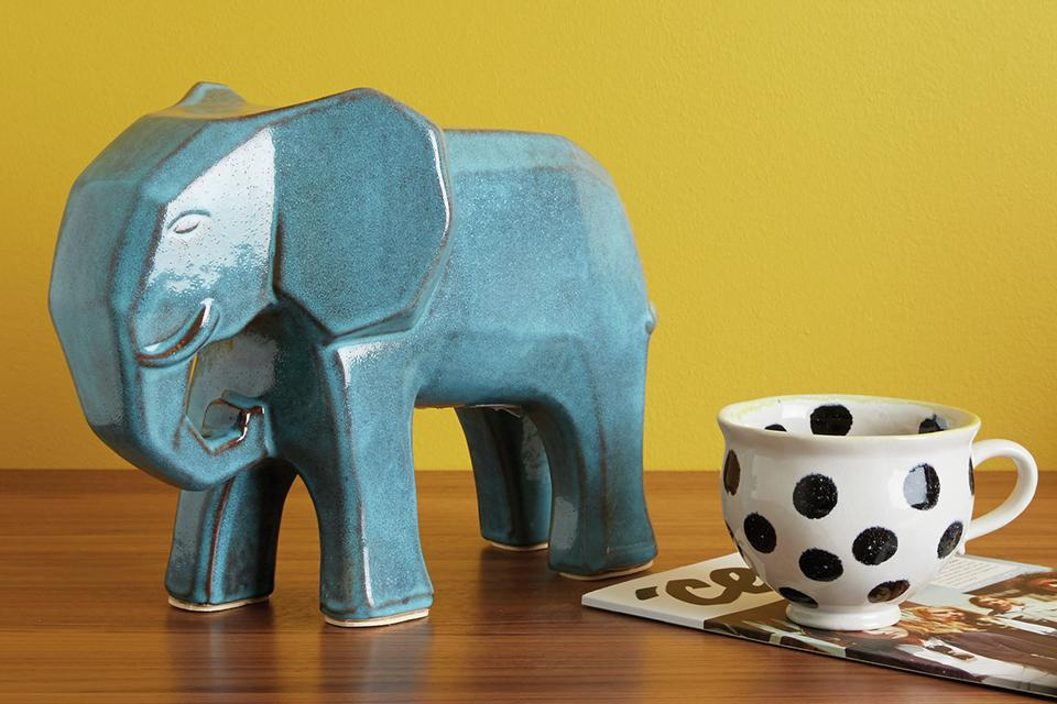 A turquoise elephant ornament on a table beside a teacup.
